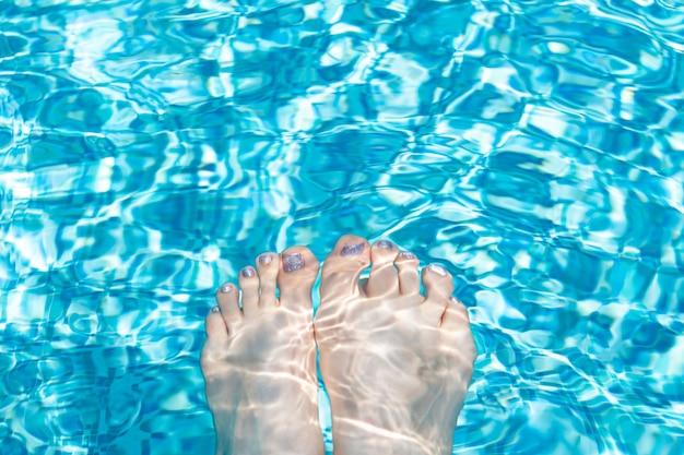 Female feet with glitter pedicure under clear pool water.