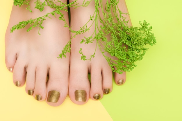 Female feet with golden nail design. gold nail polish pedicure on yellow green surface.
