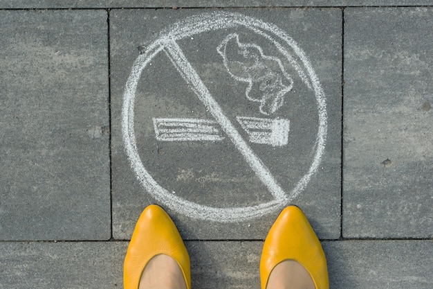 Female feet with picture no smoking painted on the grey sidewalk