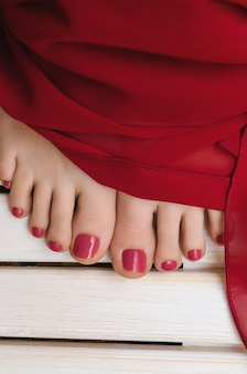 Female feet with red pedicure on wooden
