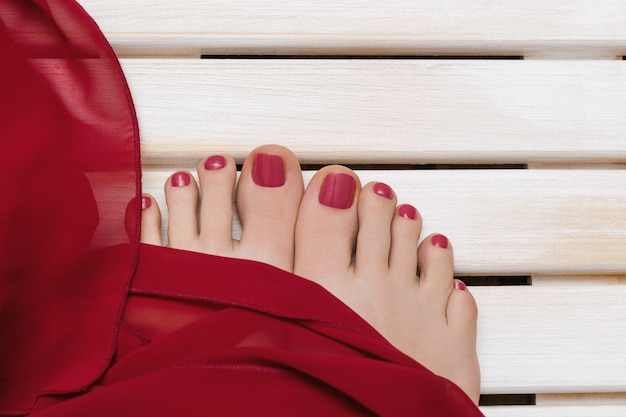Female feet with red pedicure on wooden.