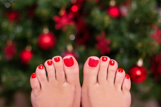 Женские ножки с красными зимними ногтями для педикюра