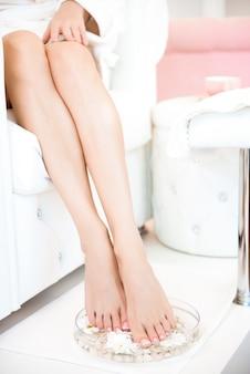 Женские ножки с чашей для спа, полотенцем и цветами на белом