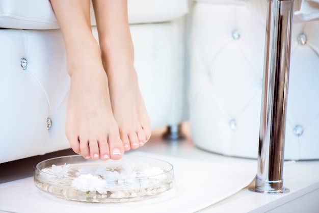 Female feet with spa bowl, towel and flowers on white background.