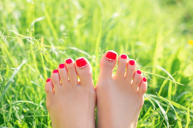 夏のペディキュアネイルを持つ女性の足は緑の草に赤いジェルポリッシュ