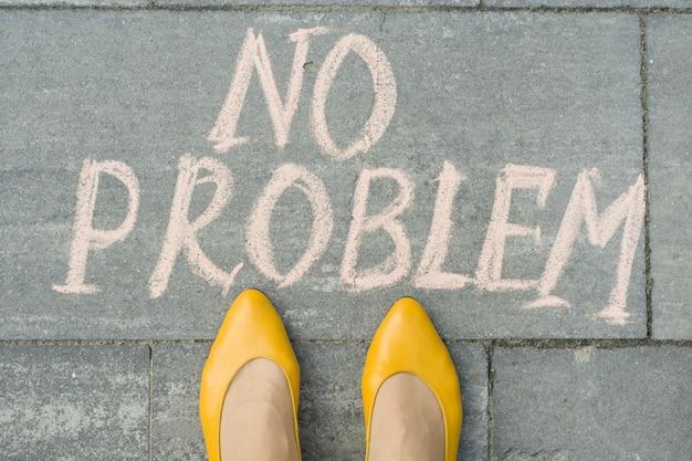 Female feet with text no problem written on grey sidewalk