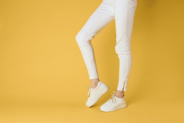 Female feet with white sneakers on yellow background