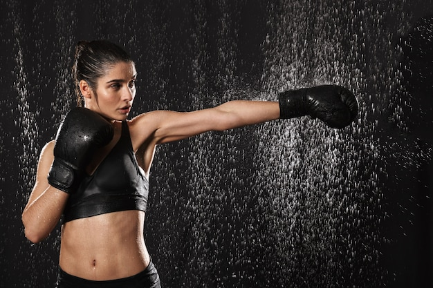 Female fighter 20s with perfect body in sportswear and black boxing gloves throwing strong punch under rain drops, isolated over dark background