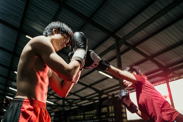 복싱 캠프에서 남성 복서와 경쟁하는 동안 펀치 모션으로 공격하는 여성 전투기