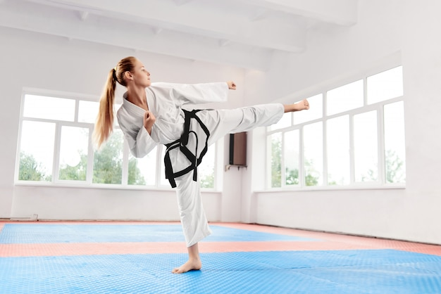 Female fighter performing kick with raised legr improving technique of fight.