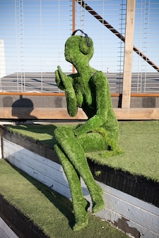 Female figure covered with artificial green grass with headphones sitting on the steps - loft project floors etagi , saint petersburg, russia, april 2021