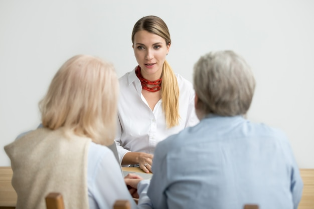Female financial advisor talking consulting senior aged couple at meeting