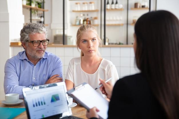 Esperta finanziaria femminile incontro con clienti giovani e maturi in coworking