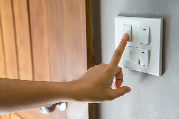 Женский палец выключается на выключателе освещения