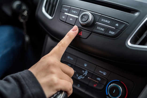 Female finger pointing on emergency stop button closeup