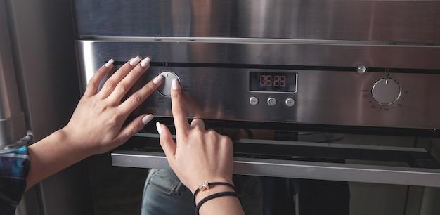 キッチンの電気オーブンのボタンに触れる女性の指。
