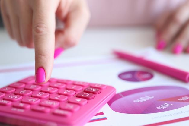 Женский палец с розовым маникюром, нажав кнопку калькулятора рядом с документами крупным планом