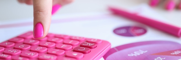 Female finger with pink manicure pressing calculator button near documents closeup