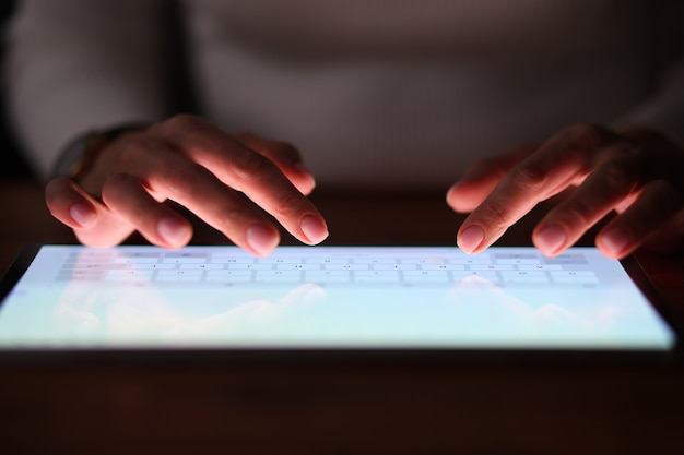 Female fingers are typing on tablet screen at night