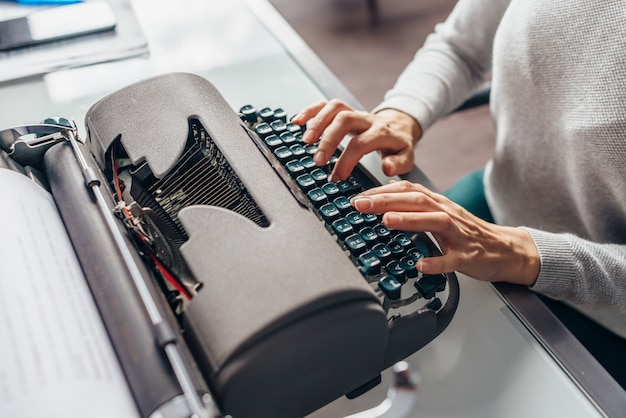 Female fingers on the keys of the typewriter type text.
