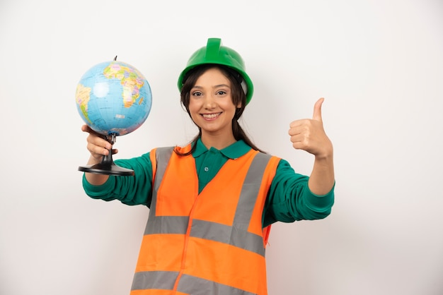 Female firefighter holding globe and making thumbs up on white background.