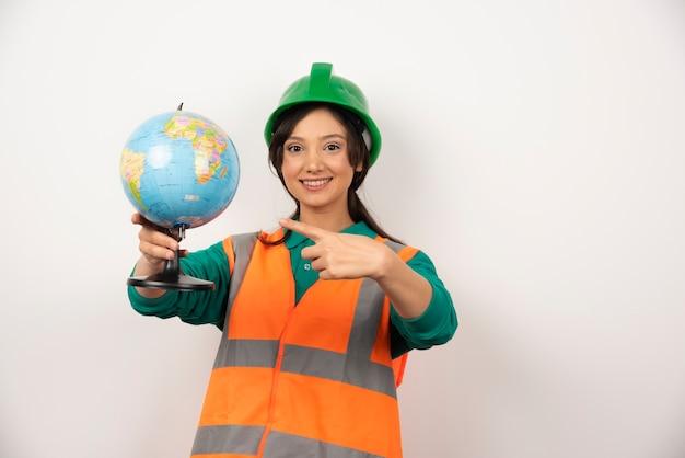 Female firefighter pointing globe on white background.