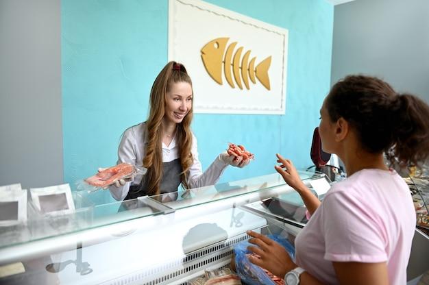 冷えた海老と紅鮭の切り身を手に持って可愛く微笑む女性魚屋さんがお客様に販売。シーフード小売。