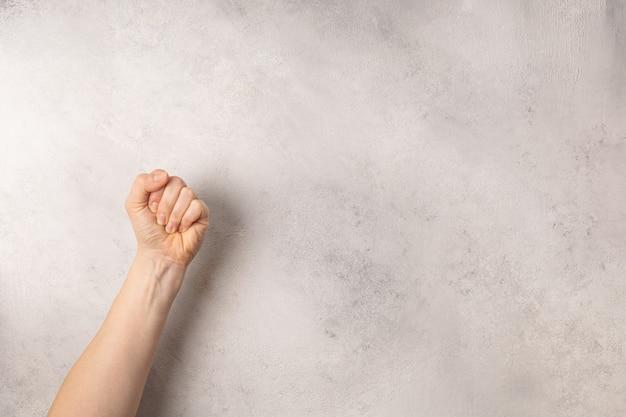 Female fist on grey background