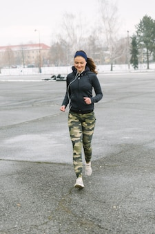 Female fitness athlete running on street