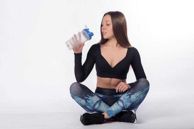 요가 포즈에 앉아 있는 여성 운동 선수와 스포츠 병, 흰색 배경에서 물을 마신다