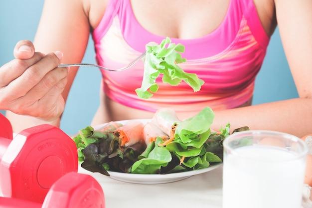 Женский фитнес, едят свежий салат и молоко, концепция здорового образа жизни