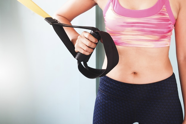 Female fitness excercise concept with copy space, trx sport equipment