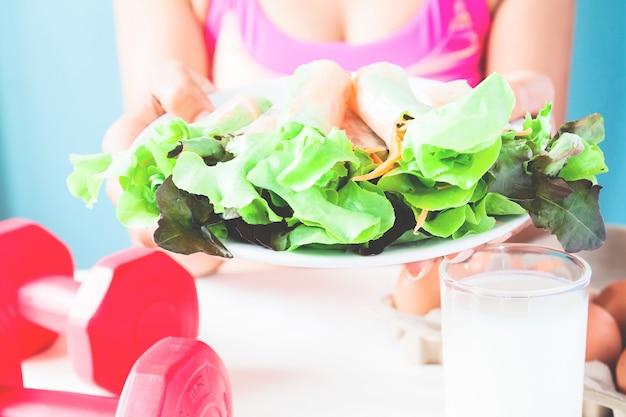Женский фитнес-холдинг салат блюдо с молоком, яйца и гантели на столе, концепция здорового образа жизни