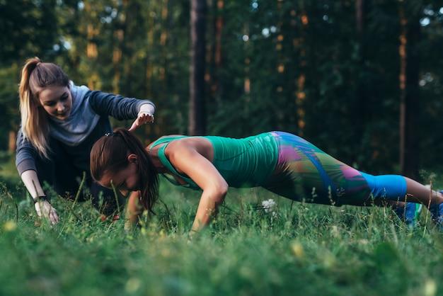 公園の芝生の上で腕立て伏せ運動を行う若い女性を支援する女性フィットネスインストラクター