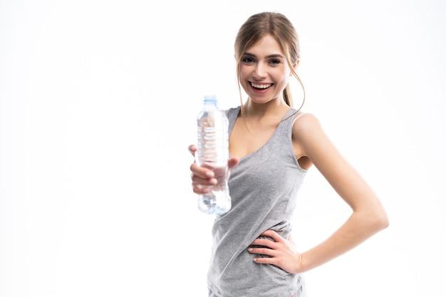 白いスタジオ環境で水筒を保持している女性のフィットネスモデル