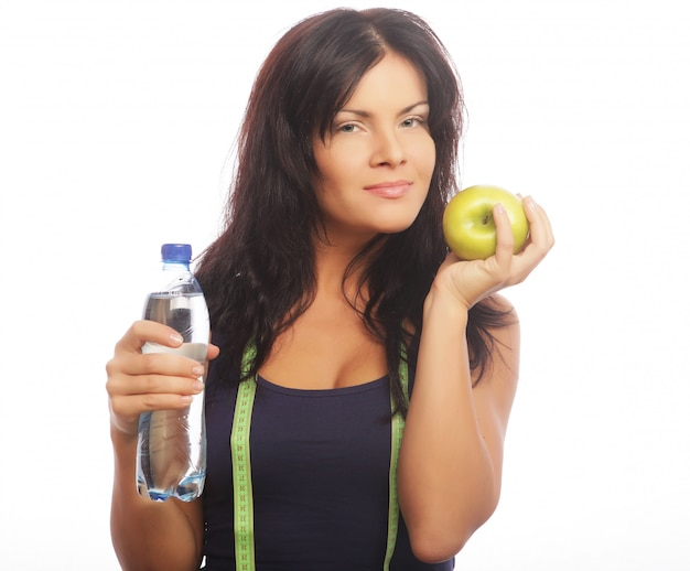 Female fitness model holding a water bottle and green apple