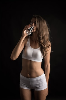 Female fitness model holding a water glass