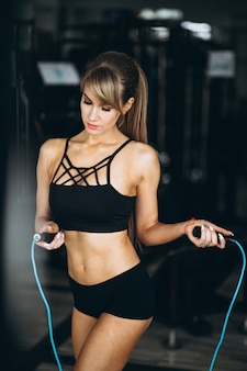 Female fitness trainer at the gym with the jump rope