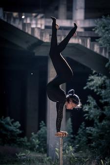 Гибкая цирковая артистка делает стойку на руках в заброшенном здании, концепция творческой индивидуальности ...