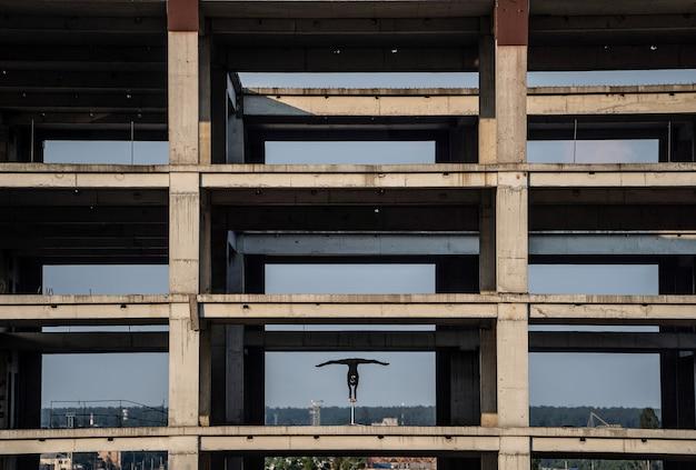 개성 창조의 버려진 건물 개념에서 물구나무서기를 하는 유연한 여성 서커스 예술가...