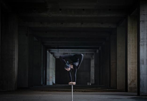 Женский гибкий цирковой артист делает стойку на руках в заброшенном туннеле. понятие силы воли, мотивации и страсти.