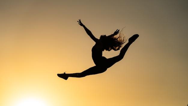 Гибкая танцовщица прыгает во время заката на оранжевом небе