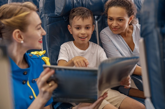 Female flight attendant entertaining a kid on board by offering a book to read. cabin crew provide service to family in airplane. airline transportation and tourism concept