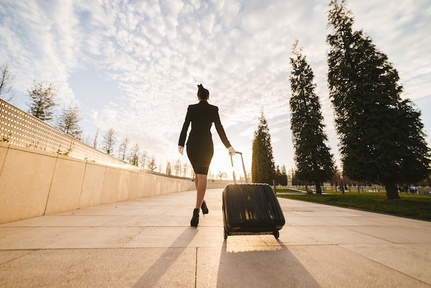 A female flight attendant in the form carries a large suitcase