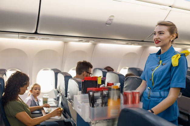 Female flight attendant serving food to passengers on aircraft. hostess walking with trolley on aisle. travel, service, transportation, airplane concept