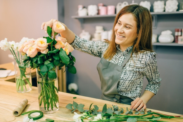 Female florist in apron puts fresh roses in a vase in flower shop, floral business concept