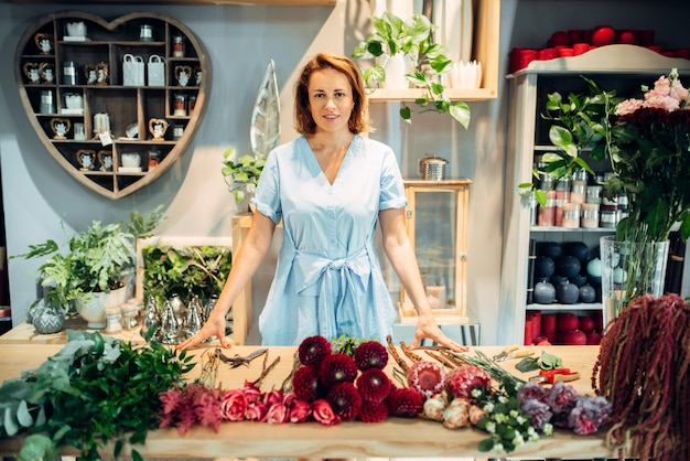 花屋でさまざまな品種の新鮮な花を持つテーブルで女性の花屋。