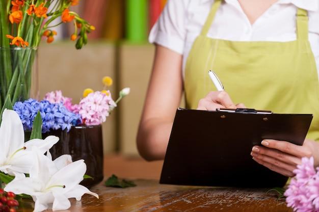 Женский флорист за работой. обрезанное изображение девушки-флориста, пишущей что-то в блокноте, стоя на своем рабочем месте