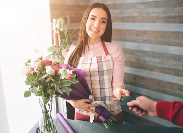 Женский флорист на работе довольно молодая темноволосая женщина делает модный современный букет из разных цветов. женщины работают с цветами в мастерской.