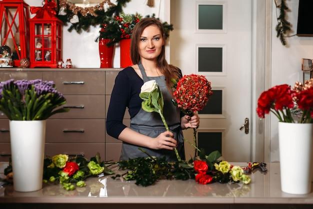 여성 플로리스트는 아름다운 꽃다발을 만듭니다.